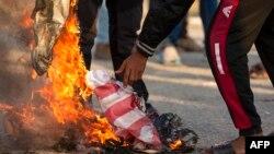 Les irakiens brulent un drapeau américain à Basra, le 30 décembre 2019.