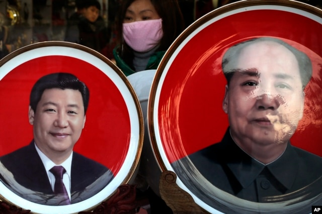 A woman looks at souvenir plates bearing images of Chinese President Xi Jinping, left, and late Chinese leader Mao Zedong on display for sale at a shop near Tiananmen Square in Beijing, Jan. 17, 2016.