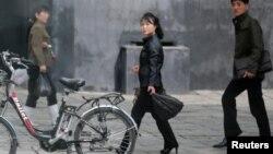 People walk past an electric bike in Pyongyang, North Korea, May 6, 2016.