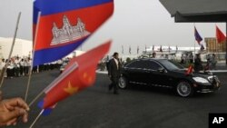 Cambodian students gather to welcome Chinese President Hu Jiantao as seen a car is escorted by bodyguards during his arrival at Phnom Penh International Airport, Phnom Penh, Cambodia, Friday, March 30, 2012. Hu on Friday arrived Phnom Penh on his four-day