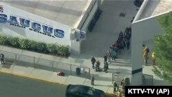 Pogled iz helikoptera na đake i osoblje koji izlaze iz srednje škole Sogus