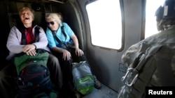Dos mujeres ríen luego de ser rescatadas y transportadas en un helicóptero militar en Colorado.