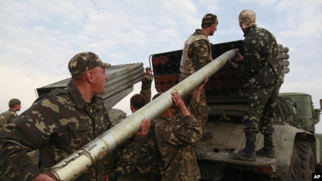 Ukrainian soldiers load a Grad missile during fighting with pro-Russian separatists close to Luhansk, eastern Ukraine, Aug. 18, 2014.