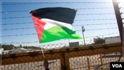 Seorang warga Tepi Barat mengibarkan bendera Palestina di pos pemeriksaan Beituniya, menunggu pembebasan 550 tahanan Palestina (18/12).