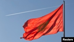 An airplane trace is seen behind a Kyrgyzstan national flag fluttering in a central square in the country's capital Bishkek.