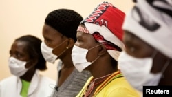 FILE - Patients with tuberculosis (TB) and HIV wear masks while awaiting consultation at a clinic in Cape Town's Khayelitsha township, South Africa.