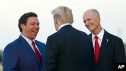 2018年10月31日美国总统特朗普在佛罗里达州迈尔斯堡空军基地与共和党州长候选人德桑提斯和佛罗里达州州长斯科特交谈。