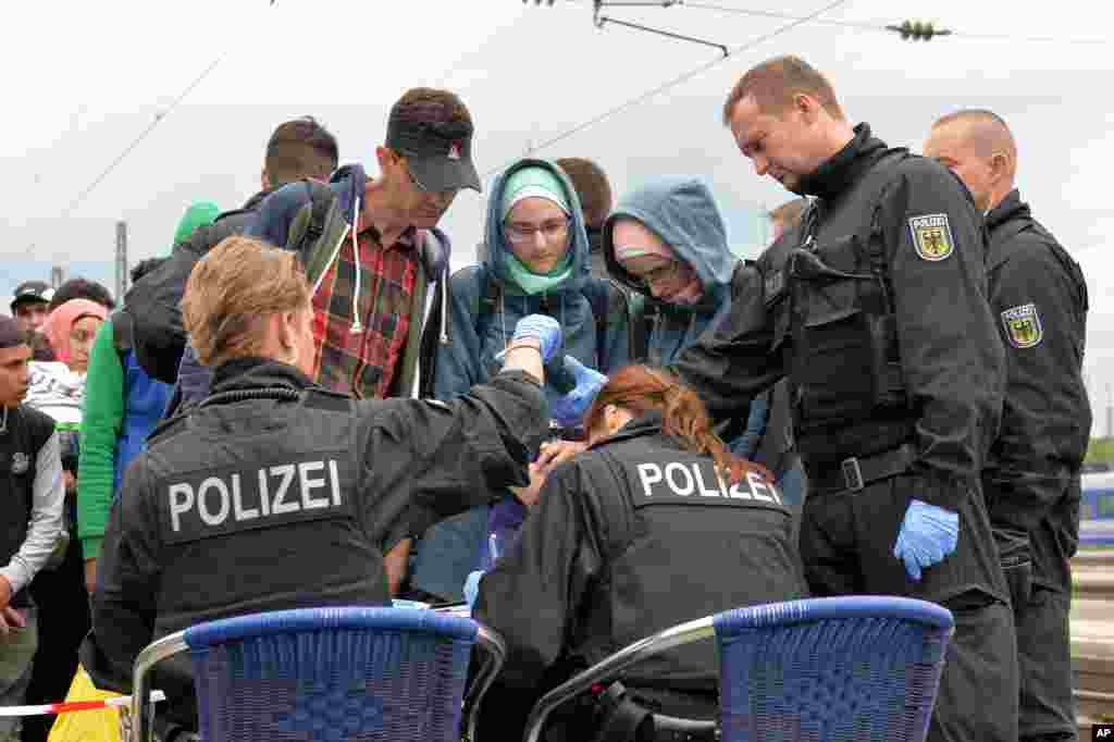 Policemen register refugees at the rail station in Freilassing, southern Germany before they take them away in busses.