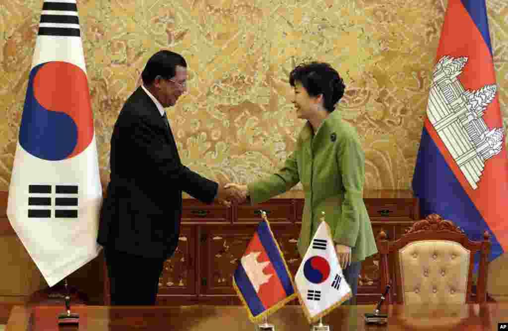 ប្រធានាធិបតីកូរ៉េខាងត្បូង Park Geun-hye (ខាងស្តាំ) ចាប់ដៃជាមួយនាយករដ្ឋមន្រ្តីកម្ពុជាលោក ហ៊ុន សែន បន្ទាប់ពីពិធីចុះហត្ថលេខាលើអនុសារណៈយោគយល់នៅវិមានប្រធានាធិបតីនៅក្រុង សេអ៊ូល ប្រទេសកូរ៉េខាងត្បូង នាថ្ងៃសៅរ៍ ទី១៣ ខែធ្នូ ឆ្នាំ២០១៤។ (AP Photo/Lee Jin-man, Pool)