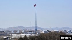 A giant North Korean flag flutters on the top of a tower in the propaganda village of Gijeongdong, North Korea, seen from South Korea, near the border village of Panmunjom, Feb. 15, 2013.