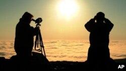 Dos personas observan a través de binoculares el tránsito de Venus frente al sol, en las montañas Cadillac, en el parque nacional Acadia, en Maine, Estados Unidos.