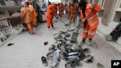 کارگران شهرداری کابل کفش های قربانیان حمله به مسجد باقر العلوم را جمع می کنند.