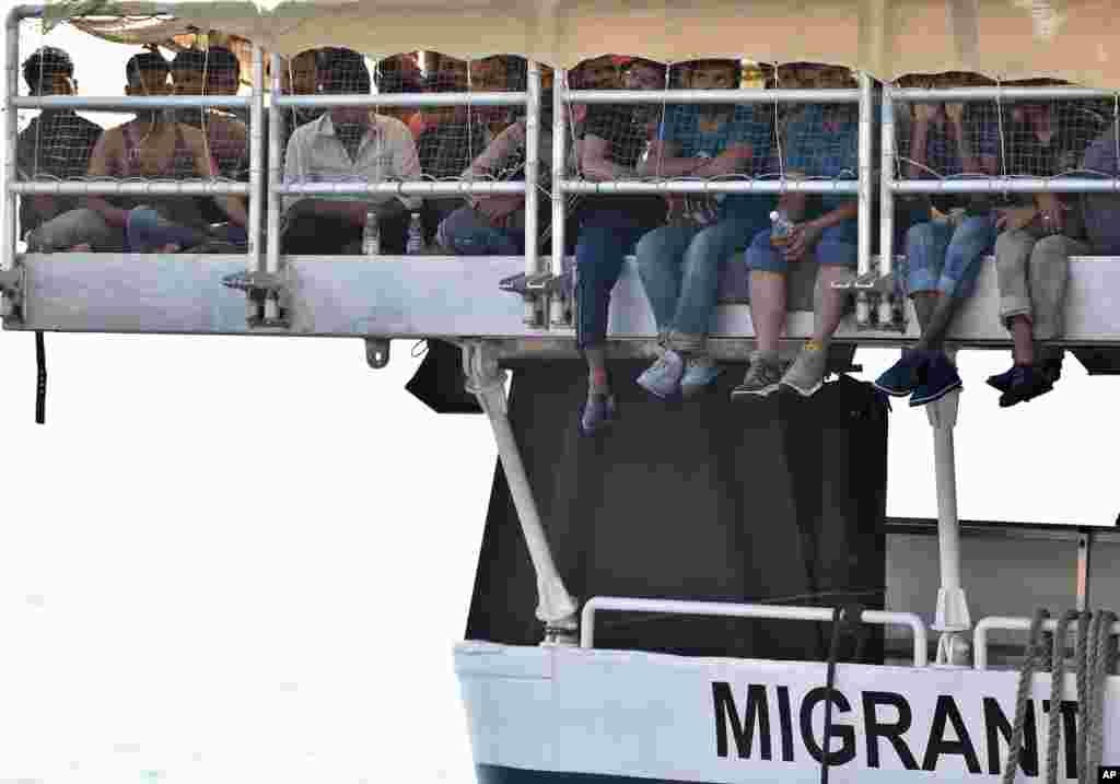 Migrants wait to disembark from the Migrant Offshore Aid Station (MOAS) vessel Phoenix, at the harbor of Messina, Sicily, Italy.