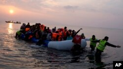 Volunteers help migrants and refugees on a dingy as they arrive at the shore of the northeastern Greek island of Lesbos, after crossing the Aegean sea from Turkey, March 20, 2016. (AP Photo/Petros Giannakouris)