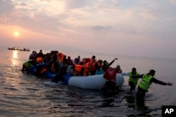 FILE - Volunteers help migrants and refugees on a dingy as they arrive at the shore of the northeastern Greek island of Lesbos, after crossing the Aegean Sea from Turkey, March 20, 2016.