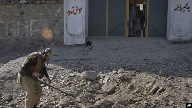 A paramilitary soldier uses a metal detector to survey the site of a bomb attack in Landi Kotal, in northwest Pakistan, December 31, 2011.