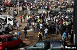 A crowd gathers at the scene of a bomb blast at a bus terminal in Nyayan, Abuja, Nigeria, April 14, 2014.