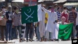 "Kashmiri protesters hold Pakistani flags, one with swords and the word ""jihad"" written on it, during a protest in Srinagar, India, July 8, 2016. Youths in the Indian part of Kashmir protested allegations that Islamic preacher Zakir Naik was involved in making hate speeches."