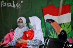 Dua pelajar berbincang sambil mengenakan masker di tengah pandemi virus corona di Banda Aceh, 10 Juni 2020. (Foto: AFP)
