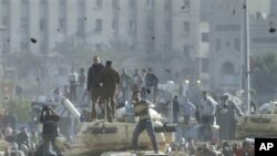 Supporters of President Hosni Mubarak, foreground , fight with anti-Mubarak protesters, rear, standing on army tanks in Cairo, February 2, 2011