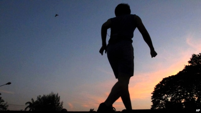 An exercise instructor is silhouetted against the dusk sky while leading a mass exercise routine at a park in Bangkok, Thailand. Every morning hundreds of health and sports enthusiasts gather in the park at the heart of the city's financial district where