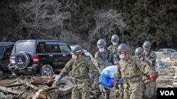 Para anggota pasukan beladiri Jepang mengevakuasi jenazah yang ditemukan di kota Noribu, Jepang utara (31/3).