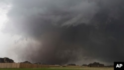 FILE - A tornado moves past homes in Moore, Oklahoma, May 20, 2013. Emergency officials in Oklahoma, Texas and Kansas are bracing for the start of what's historically the most active time of year for tornadoes while also facing wildfire threats because of severe drought conditions.