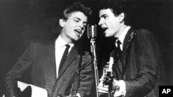 FILE - The Everly Brothers, Phil, left, and Don, perform on stage, July 31, 1964.