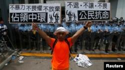 Một người biểu tình cầm áp phích 'Chiếm lĩnh Trung tâm' (trái) và 'Bất tuân Dân sự' đứng trước lực lượng cảnh sát chống bạo động bên ngoài trụ sở chính phủ ở Hồng Kông, 27/9/2014.
