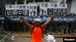 """A protester holds up placards which reads """"Occupy Central"""" (L) and """"Civil Disobedience"""" in front of a line of riot police outside government headquarters in Hong Kong, Sept. 27, 2014."""