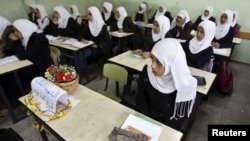 A Palestinian school girl in a Khan Younis school, November 15, 2012, sits next to the chair of a classmate who was killed during an Israeli air strike.