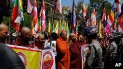 Polisi Myanmar menjaga ketat Kedutaan Thailand saat biksu dan warga Buddha melakukan aksi protes dengan memegang bendera agama dan Nasional di luar kantor tersebut, di Yangon, Myanmar, Jumat, 24 Februari, 2017. (AP Photo/Thein Zaw)