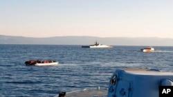Na ovoj fotografiji koju je osigurala Helenska obalna straža i snimljenoj s plovila prikazan je gumenjak s migrantima, lijevo, s turskim brodovima u pozadini, na uskom dijelu vode između istočnog grčkog otoka Lezbosa i turske obale