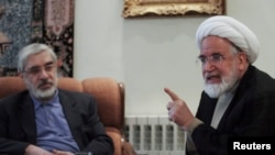 FILE - Iranian opposition leader Mirhossein Mousavi (L) meets with pro-reform cleric Mehdi Karoubi in Tehran, Oct. 12, 2009.