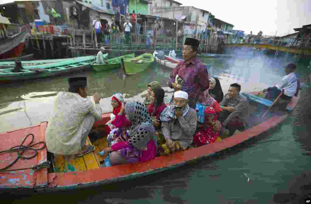 Indonesian Muslims leave their village by long boat to offer Eid al-Fitr prayers, in North Jakarta, Indonesia, July 28, 2014.