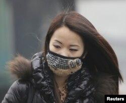 女子行走在北京冬日的浓重雾霾中(2013年1月29日)
