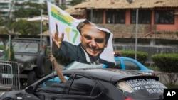 29일 브라질 리우데자네이루에서 극우파 대선후보인 자이르 보우소나루인 지지자가 차를 운전하는 도중 자이르 보우소나루 후보가 그려진 깃발을 흔들고 있다.
