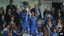 Para pemain klub Chelsea mengangkat piala Champions UEFA setelah mengalahkan klub Bayern Munich melalui adu penalti dalam final Liga Champions, Sabtu (19/5).
