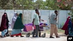 26일 소말리아 모가디슈의 대통령궁에 포탄 공격이 발생한 가운데, 희생자 가족들이 부상당한 여성을 이송하고 있다.