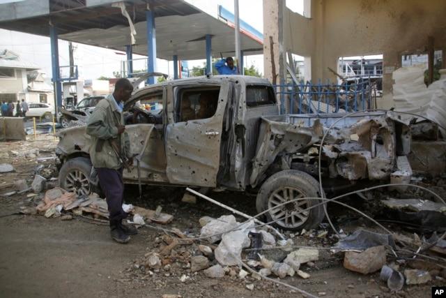 FILE - A Somali security man looks at the wreckage of a truck near the Nasahablood hotel in Mogadishu, Somalia, June 26, 2016.