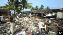 Penyintas tsunami di tengah puing-puing bangunan yang hancur di Pamadura, Kolombo selatan, Srilanka, 30 Desember 2004.