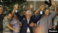 Palestinian President Mahmoud Abbas (C) holds hands with Palestinian prisoners who were released from Israeli prisons during celebrations in the West Bank city of Ramallah, Aug. 14, 2013.