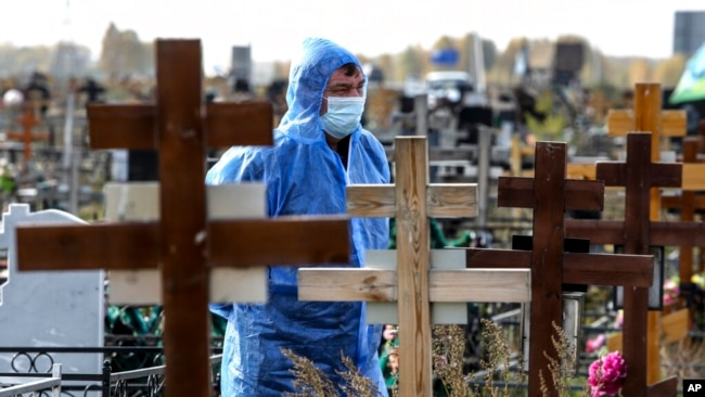 A grave digger wearing a protective suit stands during a a COVID-19 victim burial at a cemetery outside in Omsk, Russia, Oct. 7, 2021.