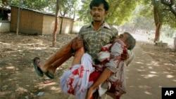 Čovek nosi povredjenu osobu nakon eksplozije pred politički skup u Patni u Indiji, 27. oktobar 2013.
