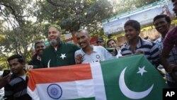 Mohammad Bashir (ketiga dari kiri), penggemar kriket dari Pakistan dan Sudhir Kumar (keempat dari kanan), warga India, membentangkan bendera India dan Pakistani yang dijahit jadi satu di depan stadion Chinnaswamy di Bangalore, India (25/12).
