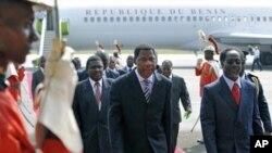 ປະທານາທິບໍດີເບນິນ (ກາງ) ໄດ້ຖືກຕ້ອນຮັບທີ່ສະໜາມບິນ ໂດຍນາຍົກລັດຖະມົນຕີ ຂອງທ່ານ Laurent Gbagbo ຄືທ່ານ Gilbert Marie N'gbo Ake (ຂວາ) ຂະນະທີ່ທ່ານເດີນທາງ ໄປເຖິງສະໜາມບິນ Abidjan (28 ທັນວາ 2010)