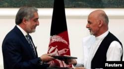 Calon presiden Afghanistan Abdullah Abdullah (kiri) dan Ashraf Ghani bertukar perjanjian yang ditandatangani untuk pembagian kekuasaan di Kabul, 21 September 2014.