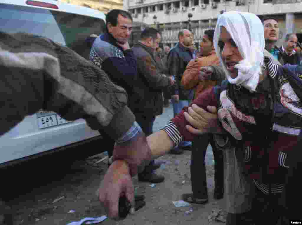 An injured police officer is assisted by people out of the damaged Cairo Security Directorate after a bomb attack in downtown Cairo, Jan. 24, 2014.