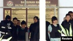 Doan Thi Huong (Vietnam) dan Siti Aisyah (Indonesia) yang diadili atas tuduhan terlibat dalam pembunuhan Kim Jong-nam, saudara tiri pemimpin Korea Utara, dikawal ketat saat meninggalkan Pengadilan Tinggi Shah Alam di pinggiran Kuala Lumpur, Malaysia, 3 Oktober 2017. (Foto: dok).
