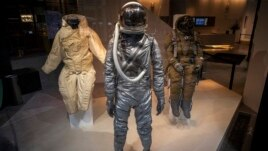A Mercury era Space Suit (C) is displayed with a Soviet full pressure Strizh Rescue Space Suit (R) as part of the upcoming Space History Sale at Bonham's auction house in New York, April 4, 2014.